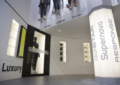 Showroom, Präsentation von Sportartikeln in beleuchteten Glasregalen und einer Glasvitrine, die Produktlinie entweder in 3D Buchstaben oder als Grafiken montiert,große Leuchtsäule