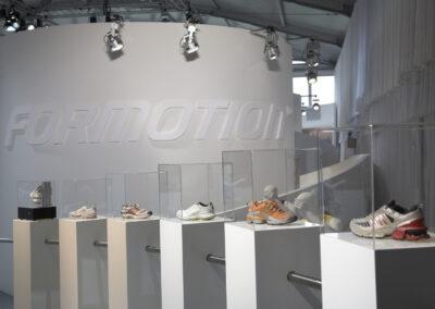 weiße halbrunde Wand mit weißen 3D Buchstaben, Scheinwerfer beleuchten die Wand, davor stehen mehrere Produktsäulen mit Schuhen im Glaskasten