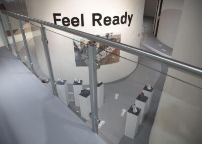 """Galerie mit Alu Geländer und Glasfront, mit Blick auf Produktsäulen mit Sportschuhen, in der Mitte große weiße Säule mit 3D Buchstaben und Bild, auf dem Boden """"Footprint"""" Grafiken"""