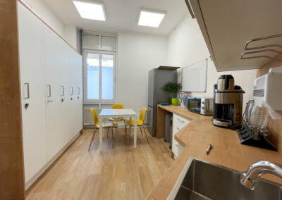 Praxis, Mitarbeiterküche, weiße Küchenzeilen- und Schrankfronten, Arbeitsplatte in Eiche Optik, abschließbare Mitarbeiterschränke, Tisch mit drei Stühlen