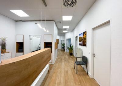 Heller Empfangsbereich, Eiche Boden und weiße Empfangstheke mit Eiche Aufsätzen, helle Beleuchtung, Regale in Eiche Optik, Sitzmöglichkeiten