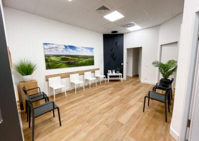 Praxis Wartebereich mit schwarzen und weißen Stühlen, Eicheholzboden und Holzleisten in Eicheoptik, stylische Hängelampe, Landschaftsbild