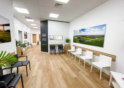 Praxis Wartebereich mit schwarzen und weißen Stühlen, Eicheholzboden und Holzleisten in Eicheoptik, Prospektschütten an der Wand, Landschaftsbild