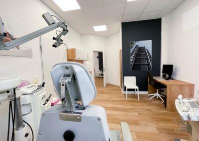Behandlungszimmer mit Behandlungsstuhl, medizinische Instrumente, Arbeitstisch mit Drehstuhl, schwarze Wand mit Gebäudebild, Behandlungszimmerschrank