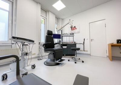helles Behandlungszimmer mit Behandlungsstuhl, medizinischen HNO Instrumenten, Tisch in Bucheoptik