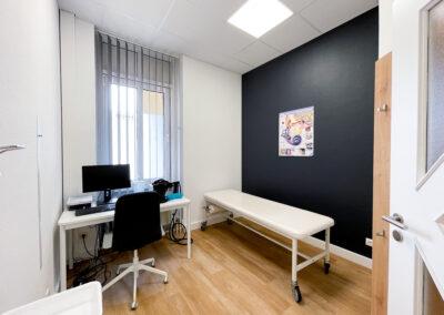 Untersuchungsraum, weißer Schreibtisch, Eicheholzboden, weiße Behandlungsliege, Garderobe aus Eichenholz, schwarze Wand mit Poster