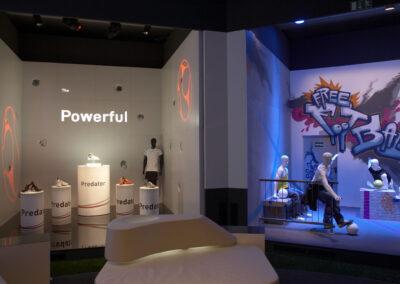 Showroom mit zwei verschiedenen Ausstellungsständen, einer im Storedesign und beleuchteten Produktsäulen, einer im Graffiti Urban Look mit sportlichen Schaufensterpuppen