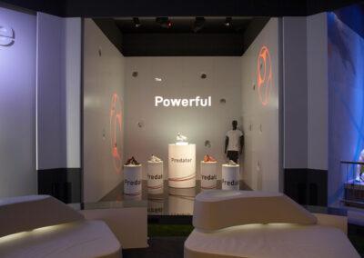 Showroom mit teils beleuchteten Säulen, auf dem adidas Schuhe ausgestellt werden und einer Schaufensterpuppe, Gobos zur Beleuchtung der Wände, weiße, beleuchtete Kunstleder Lounges