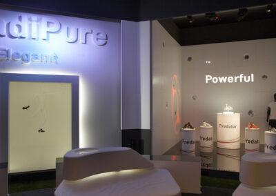 Showroom,Wandbau mit 3D Buchstaben und beleuchtetem Print-Frame-Rahmen,ein Stand mit teils beleuchteten Säulen, auf dem adidas Schuhe ausgestellt werden und einer Schaufensterpuppe