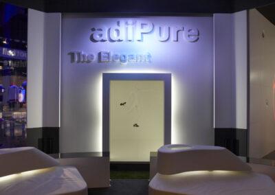 adidas Ausstellung im Showroom, weiße Wand mit weißen 3D Buchstaben, davor ein silberner beleuchteter Rahmen