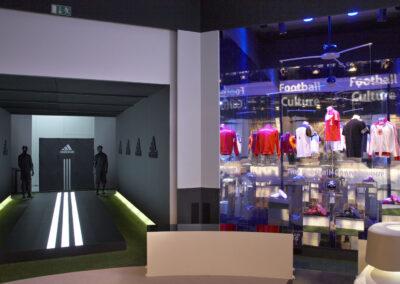 Showroom, 2 Stände: ein dunkler Stand mit Kunstrasen und schwarzem Podest mimt weiß beleuchteten adidas Streifen, Logos an der Wand, ein verspiegelter Stand mit Ausstellungsstücken
