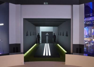 adidas Ausstellung im Showroom, dunkler Stand mit Kunstrasen und schwarzem Podest mimt weiß beleuchteten adidas Streifen, Logos an der Wand