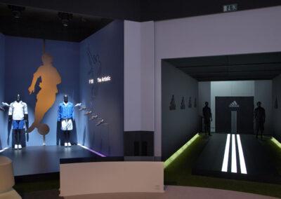 adidas Ausstellung im Showroom, zwei Stände: einer im dunklen Storedesign und der andere dunkel, beleuchtet sind nur die adidas Streifen