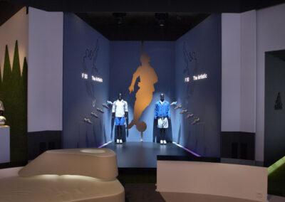 adidas Ausstellung im Showroom im Store Design mit Ausstellungstücken und Bildern an den Wänden und zwei Schaufensterpuppen