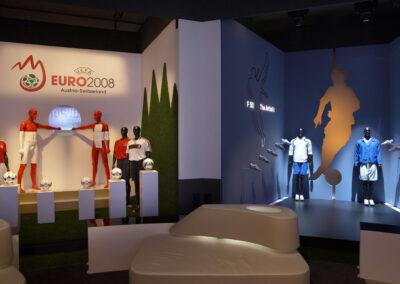 adidas Ausstellung im Showroom, zwei Stände: einer mit Säulen für Fußbälle und dahinter Schaufensterpuppen, daneben ein dunkler Stand im Storedesign