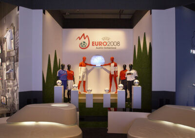 adidas Ausstellung im Showroom mit Säulen, wo Fußbälle draufliegen, Schaufensterpuppen, im Vordergrund weiße Lederlounge Möbel