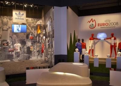 adidas Ausstellung im Showroom, einer im Store Design mit Ausstellungstücken und Bildern an den Wänden, der andere mit Säulen, wo Fußbälle draufliegen, Schaufensterpuppen