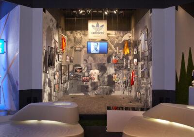 adidas Ausstellung im Showroom im Store Design mit Ausstellungstücken und Bildern an den Wänden, vor dem Stand stehen weiße Loungemöbel