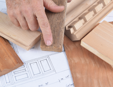 Detailaufnahme einer Schreinerhand an Holz, darunter liegen Zeichnungen