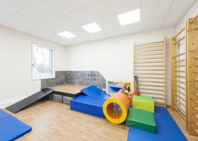 Therapieraum, mit Therapiepodest mit verstaubarer Rampe und Schubkästen im Unterbau, drei Sprossenwände an der Wand, auf dem Boden verschiedene bunte Turnmatten