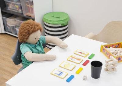 Links weißer Schiebetürenschrank mit Therapiespielzeug, Puppe auf Stuhl am weißen Kunststofftisch, auf dem sich Spiele befinden, Eiche Boden