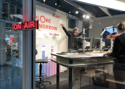 Studiosituation, on air Schild beleuchtet, Moderatoren am Moderationstisch, Studiotechnik mit Monitoren, weiße Lochplatten aus Metall, Grafiken und Logo