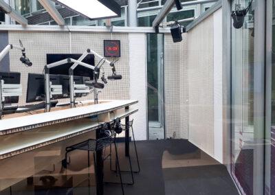 Studio, Tischbau aus Leichtbauplatte: mit einer beschichteten Rohspanplatte als Decklagen und einem ressourcenschonenden Kartonwabenkern, Barhocker, Tontechnik, Glaswand
