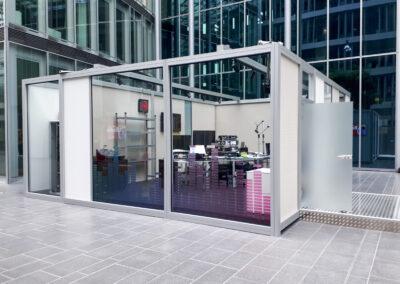 Studiokabine aus Standard Messestandsystem aus Alu mit Glastrennwänden, weiße Lochplatten aus Metall, im Inneren der Kabine: Tontechnik, Monitore