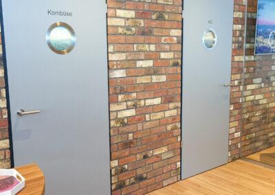 Bistrobereich, Türen zur Küche und zum Gäste WC mit Bullauge, Glastrennwand, Holzboden, Wand in Klinkeroptik