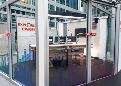 Studio, ON AIR Schild beleuchtet, Moderationstisch, Studiotechnik mit Monitoren, weiße Lochplatten aus Metall, Grafiken und Logo