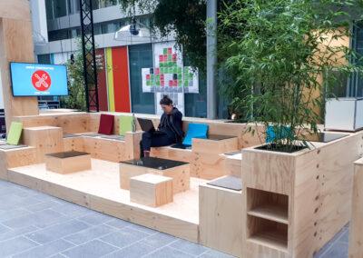 Lounge, Sitzmöglichkeiten aus Seekiefer Sperrholz, Tischplatten aus Glas, Sitzflächen mit grauem Filz, bunte CI farbene Kissen, Monitor, Traversen und grüne Pflanzen