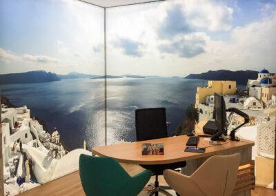 Reisebüro, beleuchteter Beratungstisch mit Monitor und zwei Stühlen für Kunden, deckenhohe Wandgrafiken, Motiv Urlaub Griechenland