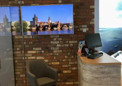 Reisebüro, Empfangstheke in Betonoptik mit Eicheplatte für DB Tickets, Monitor an Wand, Wand in Klinkeroptik
