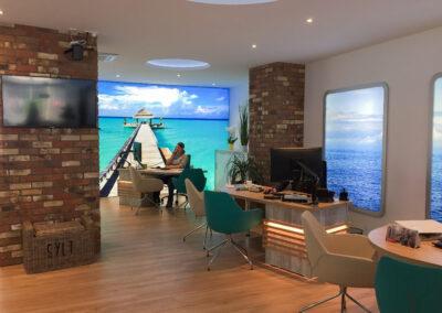 Reisebüro, Beratungstische mit Stühlen, Säulenverkleidung mit integriertem Druckerschrank und Monitor, Korbhocker, beleuchtete Wand Grafiken in Print Frame Alurahmen, Sideboard