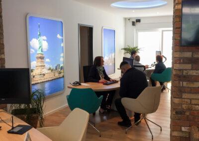 Reisebüro, Beratungstische mit Stühlen, Säulenverkleidung mit integriertem Druckerschrank und Monitor, beleuchtete Wand Grafiken in Print Frame Alurahmen