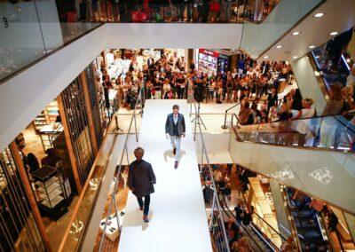 Modenschau Herrenmodenschau in einem Kaufhaus, Zuschauer stehen auf Rolltreppen