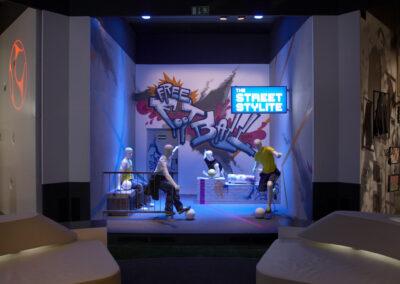 Showroom im Graffiti Urban Look, fußballspielende Schaufensterpuppen, Monitor an der rechten Wand, weiße beleuchtete Kunstleder Lounges