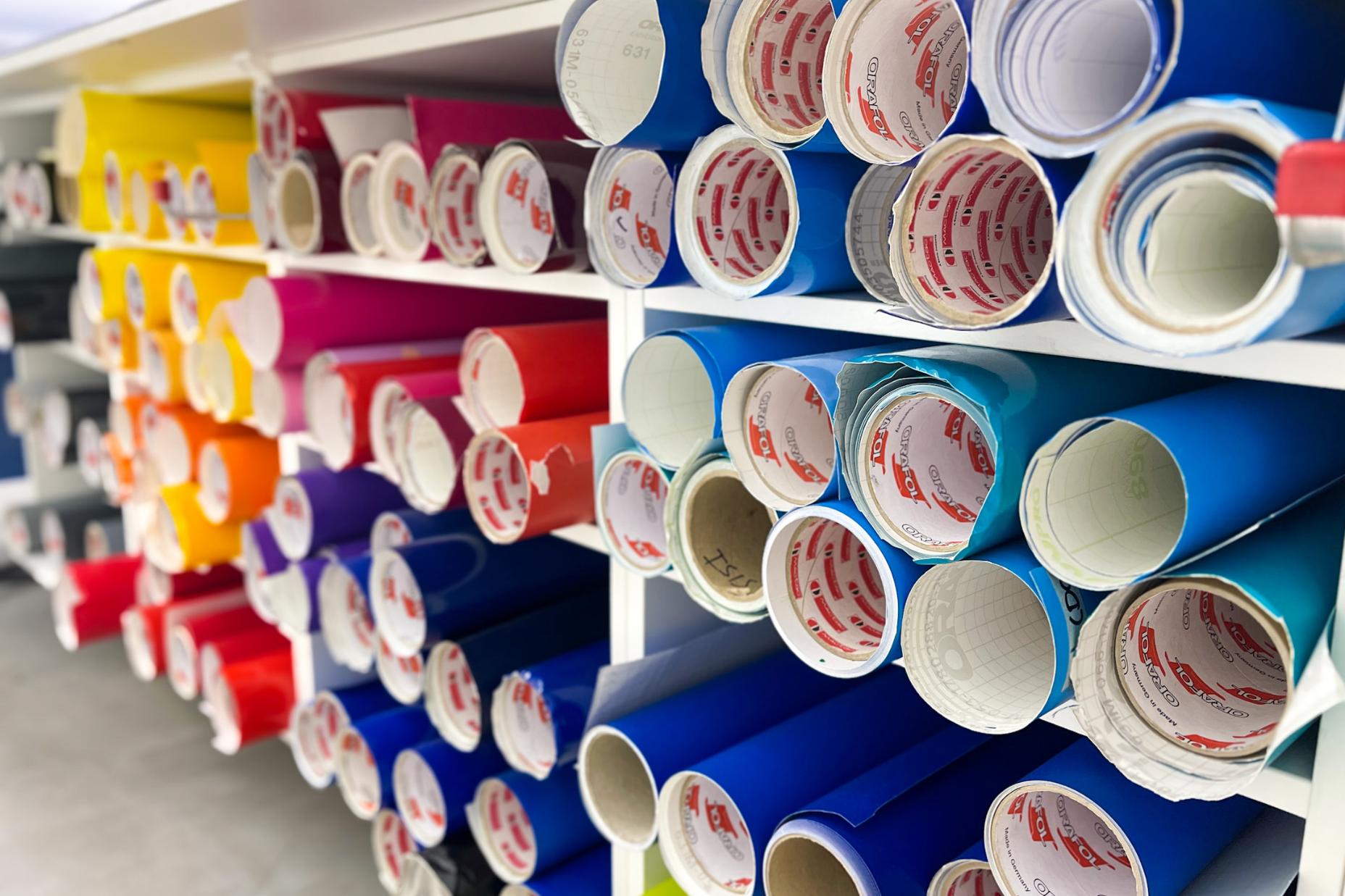 Verschiedene farbige Folienrollen im Regal der Werbetechnik