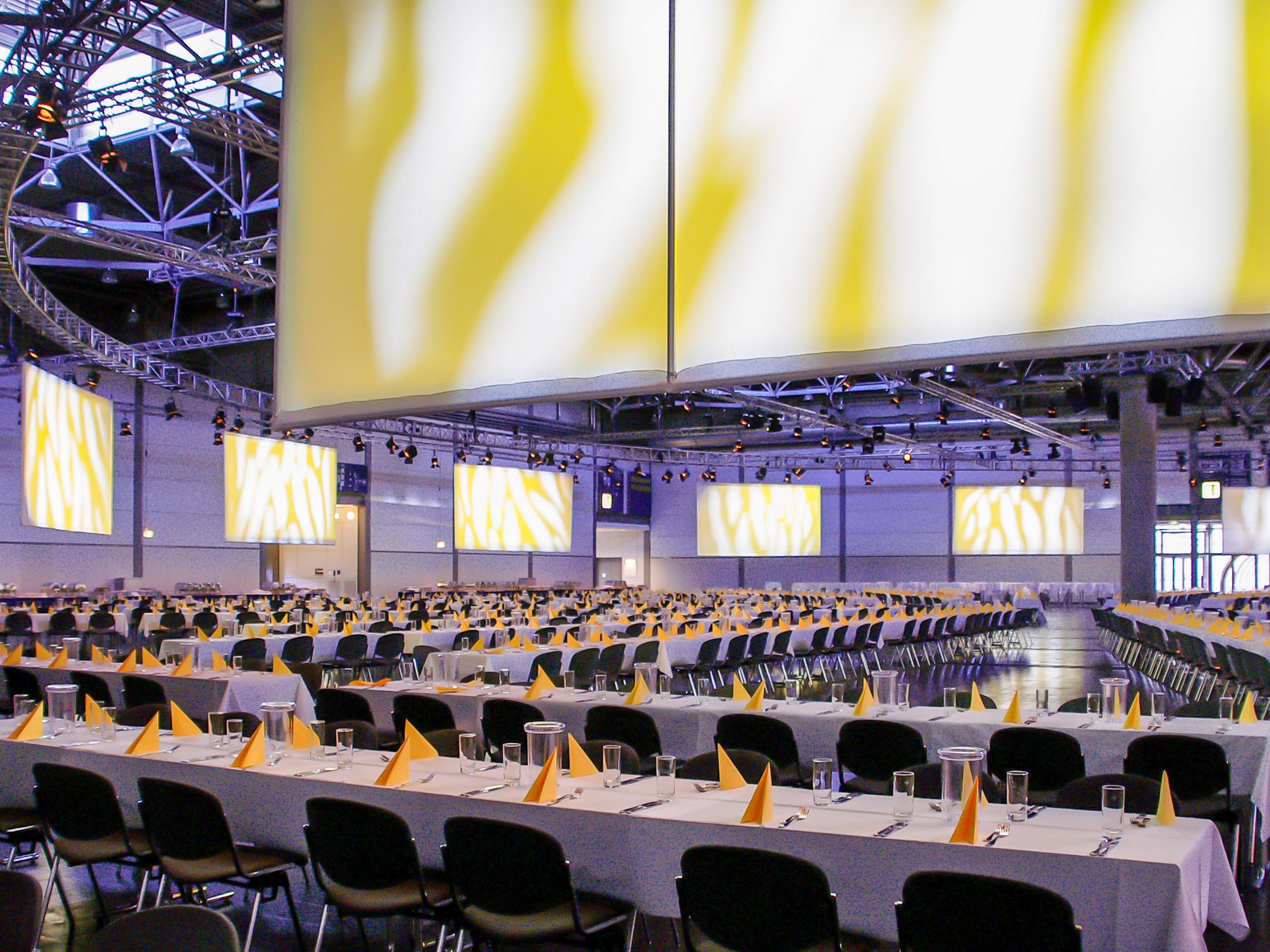 Veranstaltungshalle mit gedeckten Tischen, Traversenkonstruktion mit abgehängten Leinwänden und Scheinwerfern