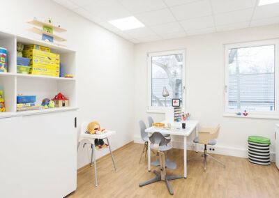 Therapieraum mit weißen Wänden und einem hellen Eiche Holzboden, einem weißen Kunststoffschrank mit Schiebetüren, wo Spielzeug verstaut ist