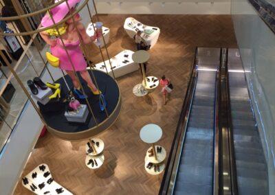 Breuninger in Düsseldorf, weiße Exponat-Tische mit Schuhen, von der Decke abgehängter goldener Käfig mit Frauen Kunststoffpupe, Highheels und einem kleinen Hund auf einem Schuhkarton