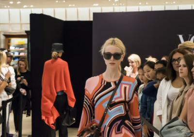 Damenmodenschau, zwei Models und Zuschauer am Rand des Laufsteges, schwarze Rückwand